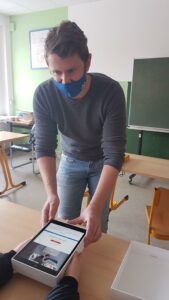 Herr Bacher übergibt iPad